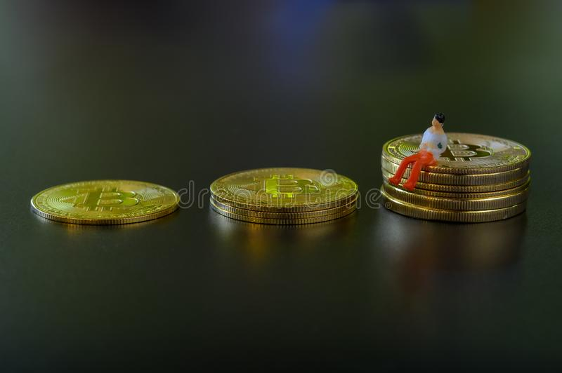 Miniature people, small model human figure sitting on golden Bitcoins on dark background with copyspace for your text. stock photos