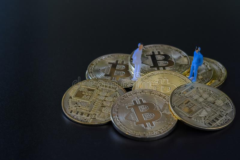 Miniature people, small model human figure standing on golden Bitcoins stack with copyspace for your text. Cryptocurrency or stock images