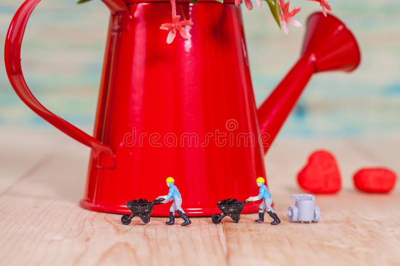 Miniature people or small people model work. With garden watering can stock photos