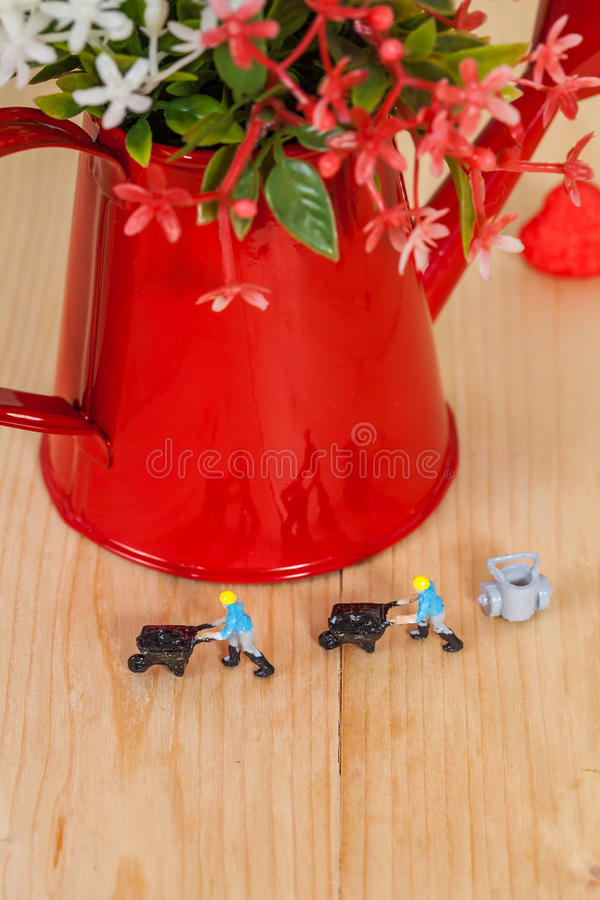 Miniature people or small people model work. With garden watering can stock photography