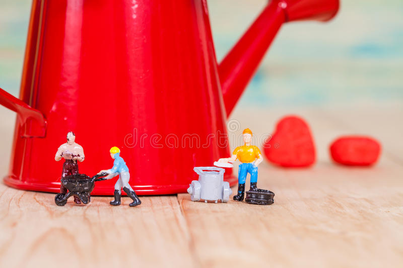 Miniature people or small people model work. With garden watering can stock images