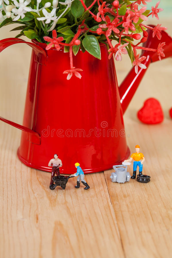 Miniature people or small people model work. With garden watering can stock photo