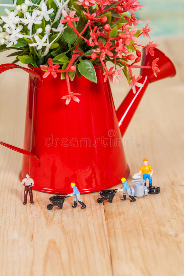 Miniature people or small people model work with. Garden watering can royalty free stock photo