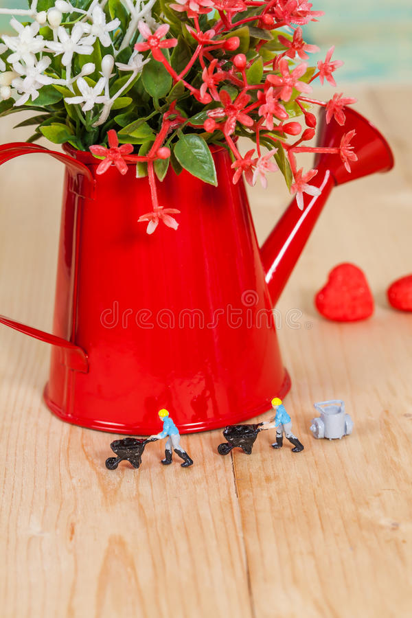 Miniature people or small people model work with. Garden watering can stock photo