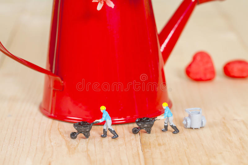 Miniature people or small people model work. With garden watering can royalty free stock photos