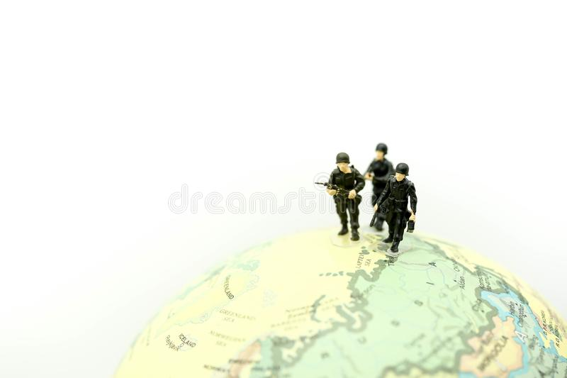 Miniature people : soldiers team with world map,War, army, military, guard concept. royalty free stock images