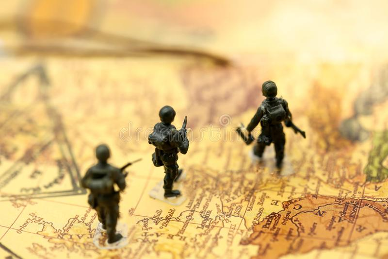 Miniature people : soldiers team with world map,War, army, military, guard concept. royalty free stock photos