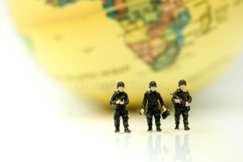 Miniature people : soldiers team with world map,War, army, military, guard concept. stock photo