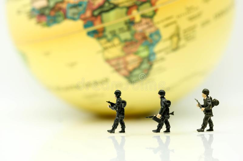 Miniature people : soldiers team with world map,War, army, military, guard concept. stock image