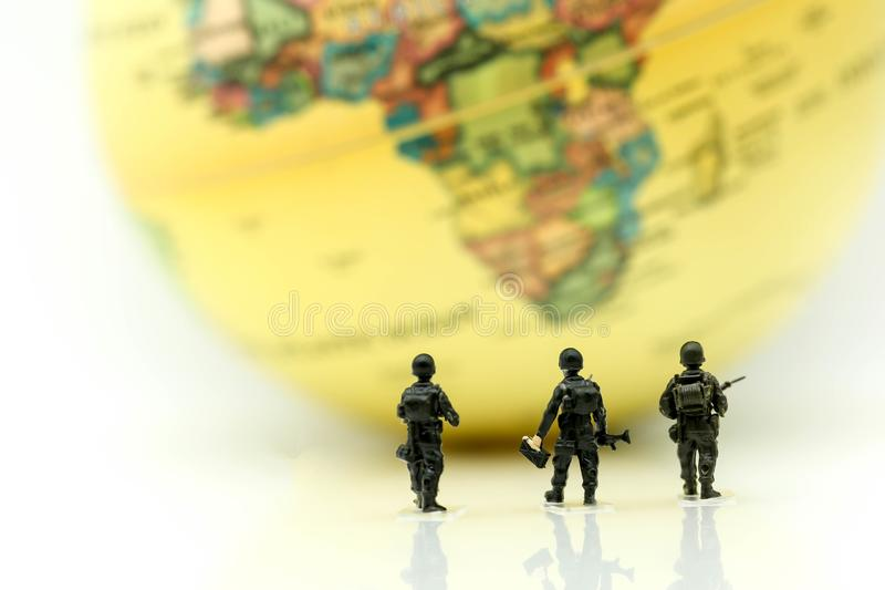 Miniature people : soldiers team with world map,War, army, military, guard concept. stock photos