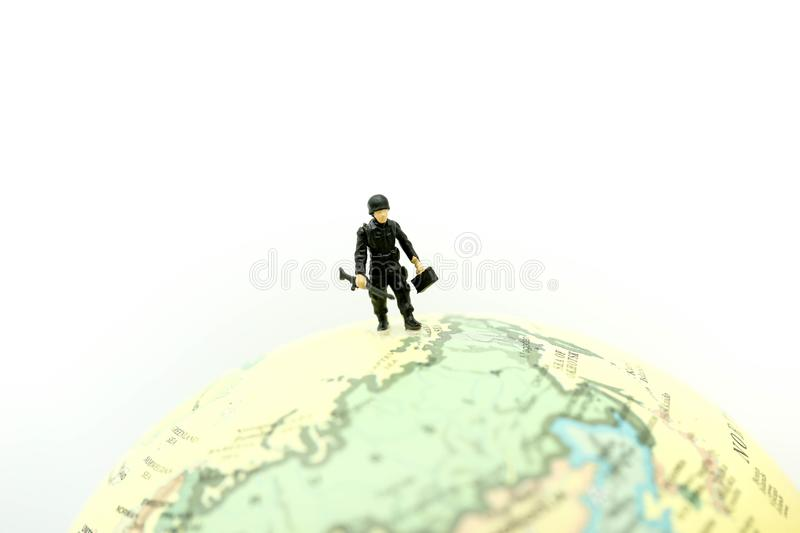 Miniature people : soldiers team with world map,War, army, military, guard concept. royalty free stock photography