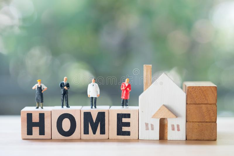 Miniature people stand on wood block  words HOME, concept of property related business. Miniature people stand on wood block  words HOME, concept of depicts a stock images