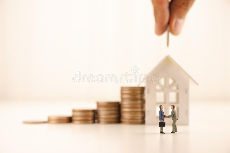 Concept save money financial business investment. Miniature people standing and handshake for successful of investment deal with coin growing growth saving money royalty free stock images