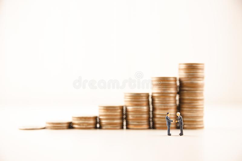 Concept save money financial business investment. Miniature people standing and handshake for successful of investment deal with coin growing growth saving money royalty free stock photos