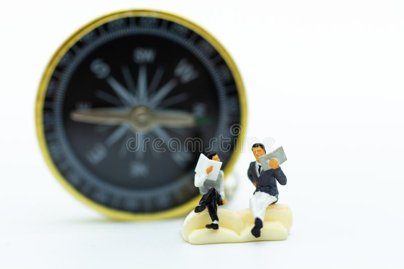 Miniature people : Student reading book and have compass to background. Image use for the direction of the study.  royalty free stock image