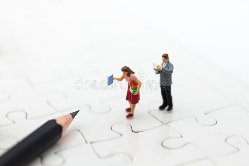 Miniature people: Students read books on the jigsaw board and pencil. Image use for education concept.  royalty free stock photos