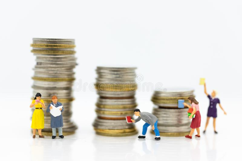 Miniature people: Students read books, keep books on bookshelves with stack of coins . Image use for education concept.  stock photography