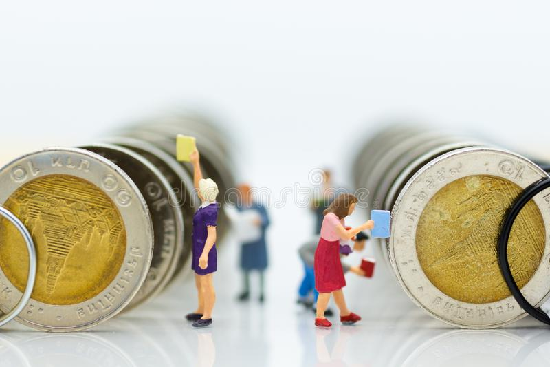 Miniature people: Students read books, keep books on bookshelves made of coins. Image use for education concept.  stock photo