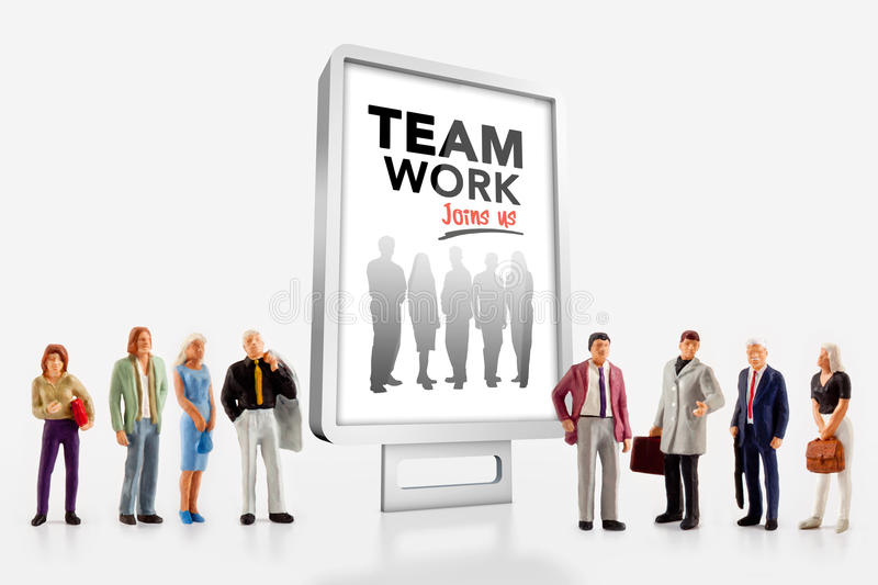 Miniature people and team work. Miniature people in front a billboard about team work stock photo