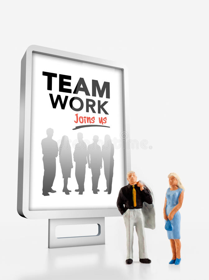 Miniature people and team work. Miniature people in front a billboard about team work royalty free stock images