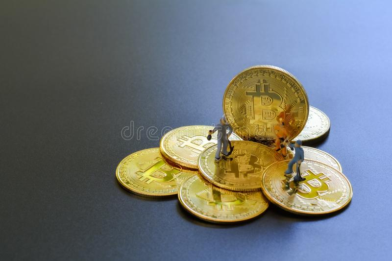 Miniature people teamworks, small model human figure standing and digging on golden Bitcoins with copyspace for your text. stock photography