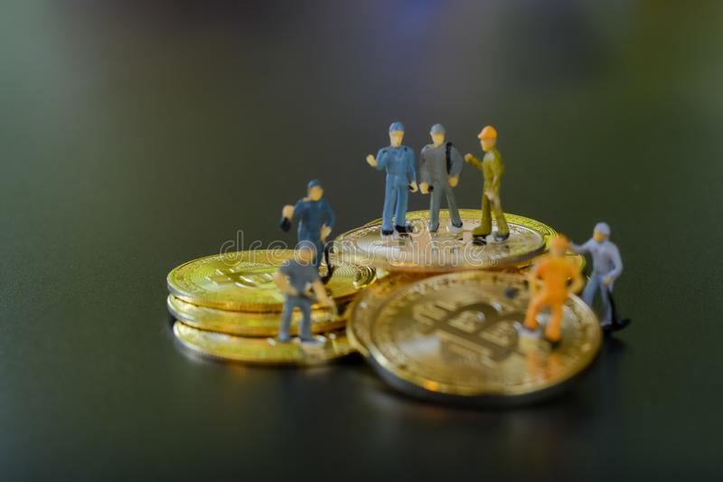 Miniature people teamworks, small model human figure standing and digging on golden Bitcoins with copyspace for your text. royalty free stock photo