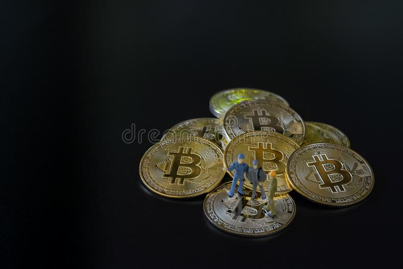 Miniature people teamworks, small model human figure standing on golden Bitcoins stack with copyspace for your text. stock photo