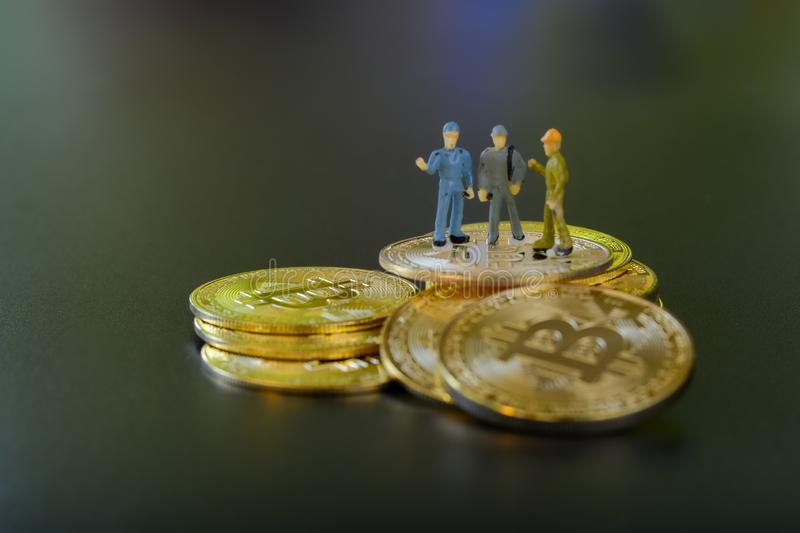 Miniature people teamworks, small model human figure standing on golden Bitcoins stack with copyspace for your text. royalty free stock photography