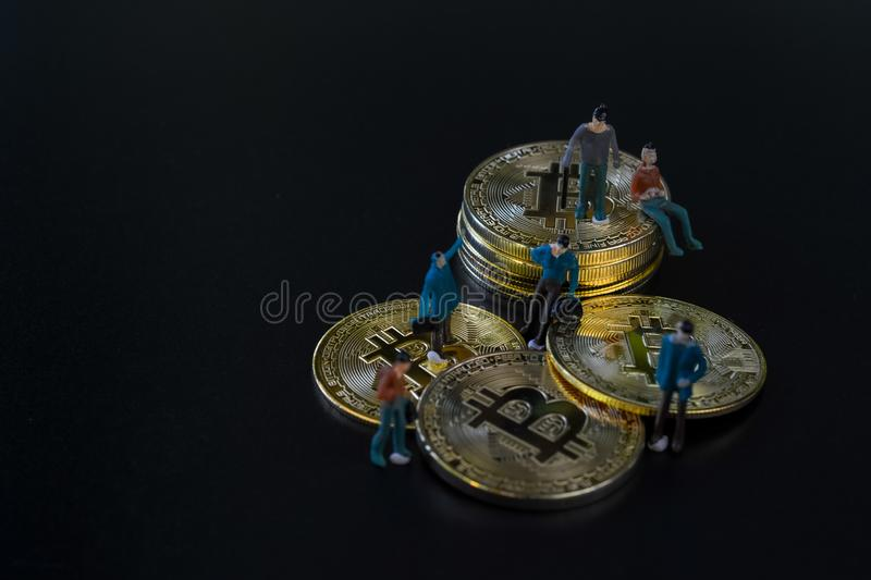 Miniature people teamworks, small model human figure standing and sitting on golden Bitcoins stack with copyspace for your text. stock photo