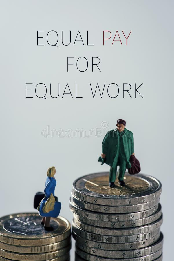 Miniature people and text equal pay for equal work. A miniature woman and a miniature man on the top of two different piles of euro coins, the man on the highest royalty free stock photography