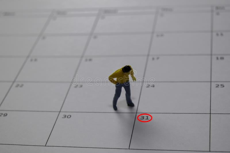 Miniature people thingking salary and looking at down 31 date end of a month stock images