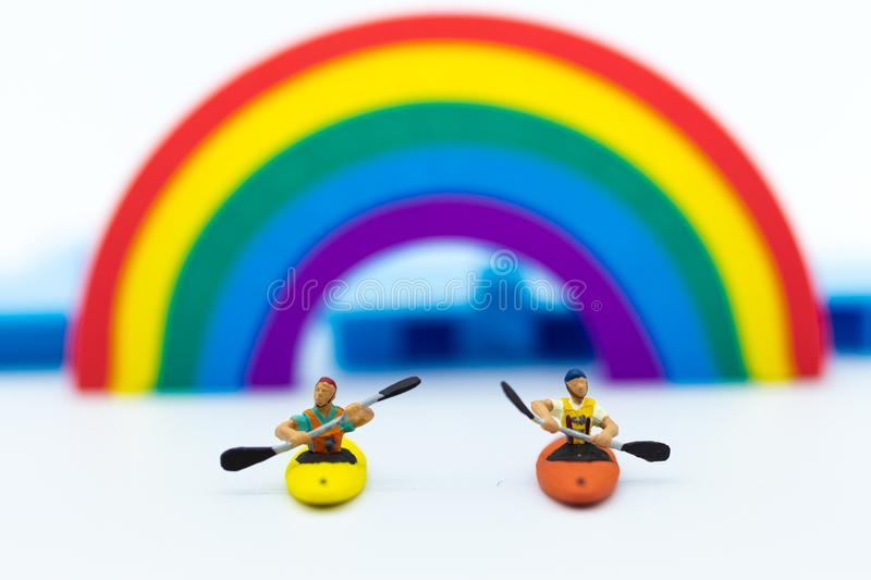Miniature people : Tourist ride Kayaking along the rainbow. Image use for travel concept stock image