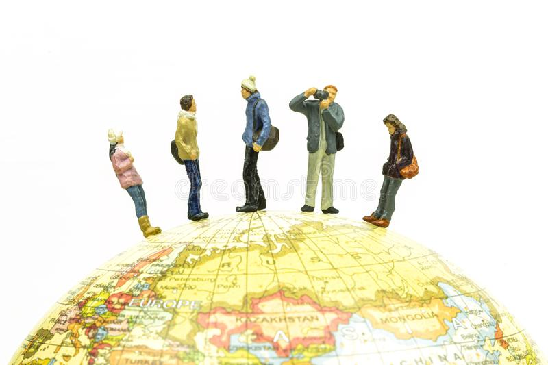 Miniature people travel around the globe close up. Image concept stock photos