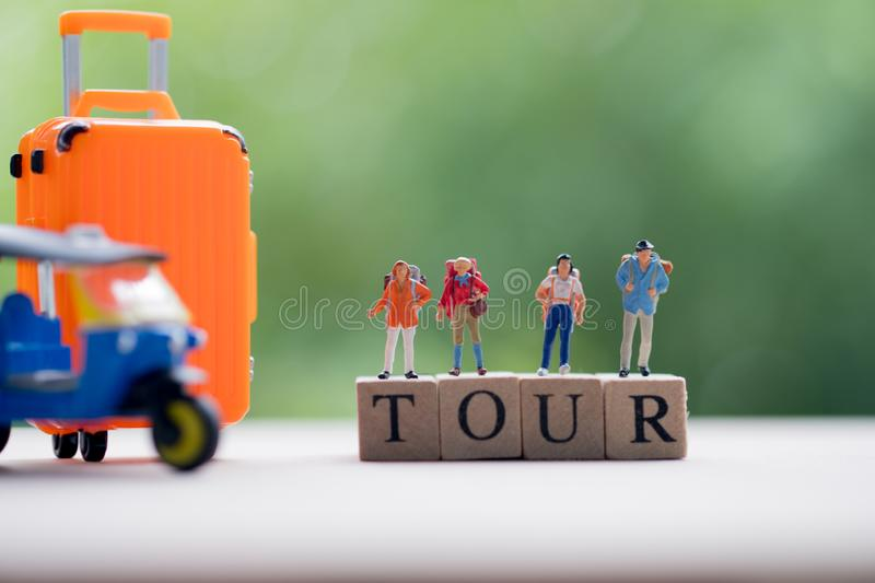 Miniature people : Traveler with backpack standing on wooden word TOUR with nature background royalty free stock images