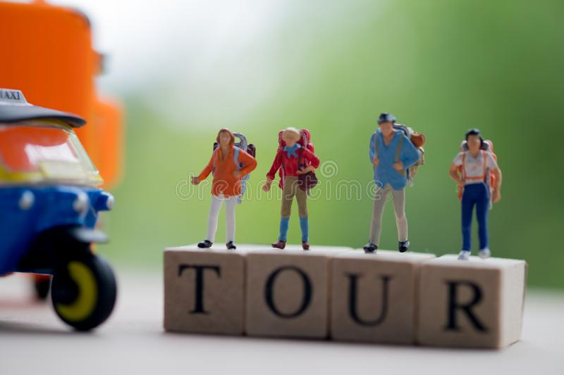 Miniature people : Traveler with backpack standing on wooden word TOUR with nature background stock photos