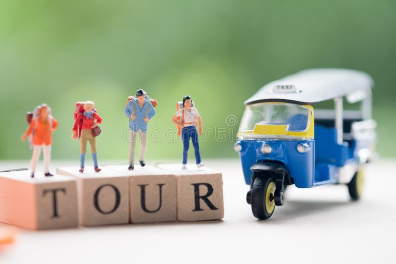Miniature people : Traveler with backpack and tuk-tuk car royalty free stock photo