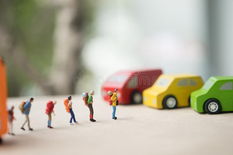 Miniature people : traveler standing on road for hopping find passing car carrying to transfer station when in travel stock photo