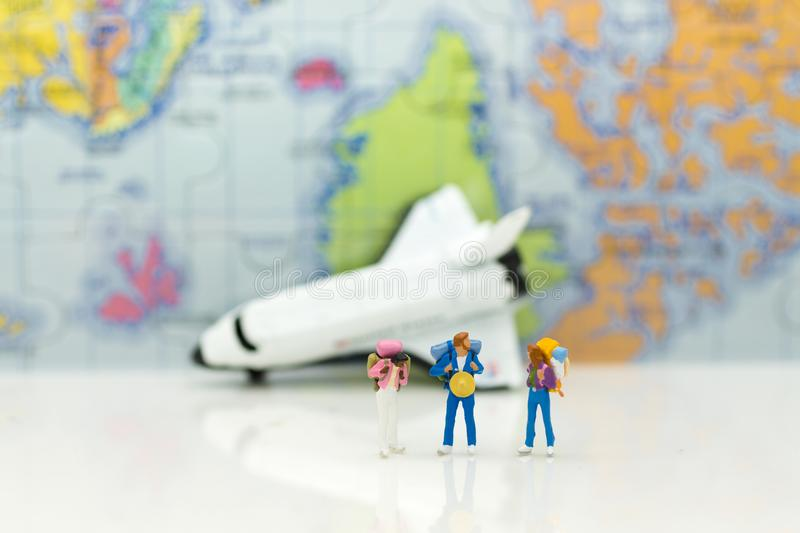 Miniature people travelers with backpack standing on world map download miniature people travelers with backpack standing on world map travel by plane image gumiabroncs Images