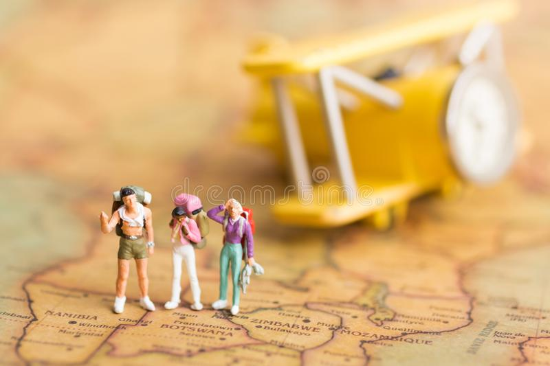 Miniature people travelers with backpack standing on world map download miniature people travelers with backpack standing on world map travel by plane used as gumiabroncs Image collections