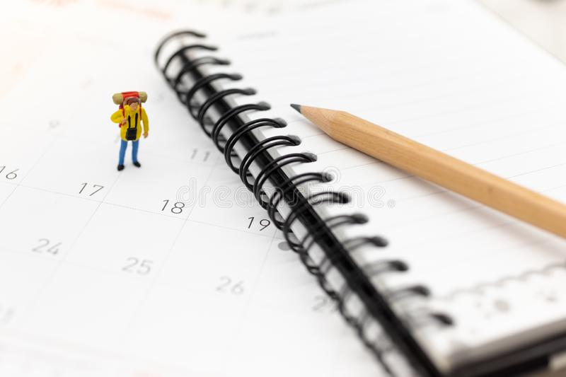 Miniature people, travelers standing on the calendar, mark date for traveling to destination. Used in the travel business concept stock photos