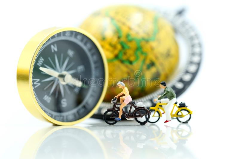 Miniature people : Travellers ride bicycle with compass and world map,travel relax concept. royalty free stock photography