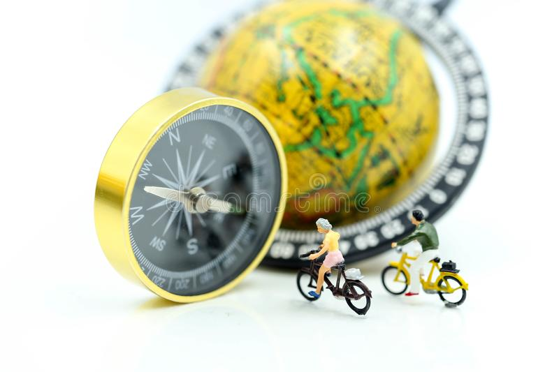 Miniature people : Travellers ride bicycle with compass and world map,travel relax concept. stock image