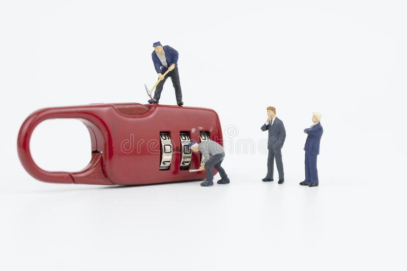 Miniature people try to unlock key. Security concept stock images