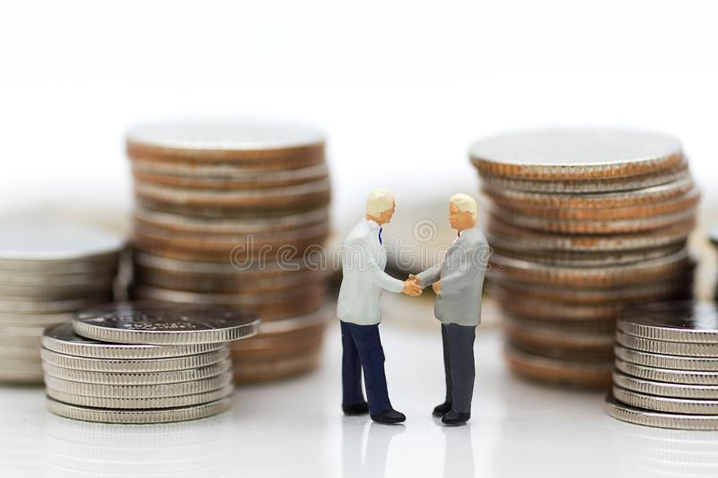 Miniature people : Two businessmen make a deal, with stack of coins to background, using as commitment, agreement, saving, finance royalty free stock image