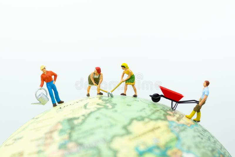 Miniature people: The villagers are farming on the globe. Image use for Industrial and agricultural stock image