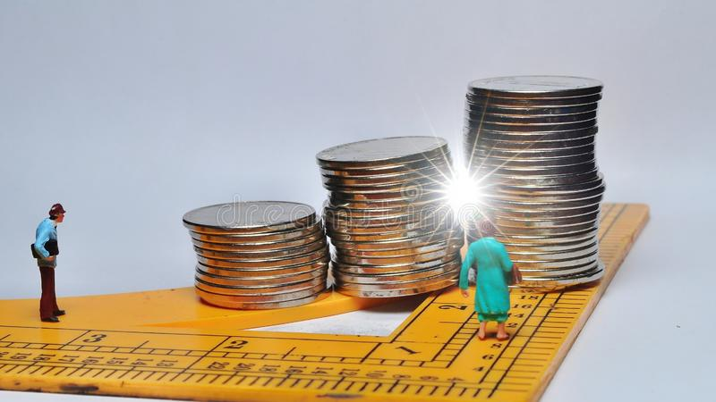 Miniature People walking on ruler with coin stacks. stock photo
