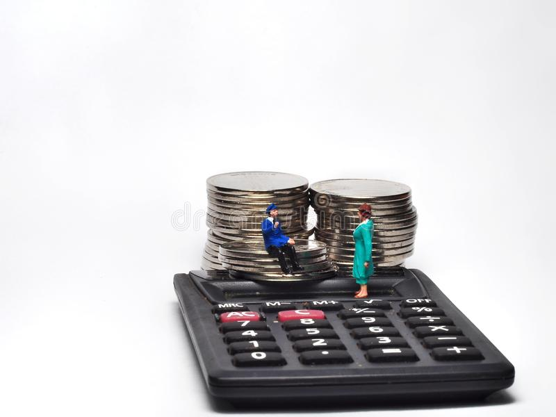 Miniature People walking on ruler with coin stacks. Concept of business people work calculated to success stock photos
