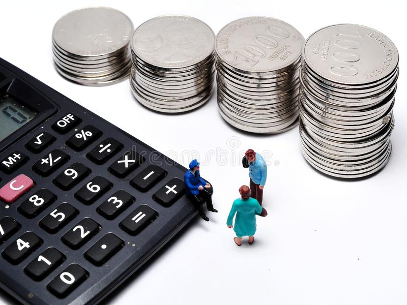 Miniature People walking on ruler with coin stacks. Concept of business people work calculated to success stock photography