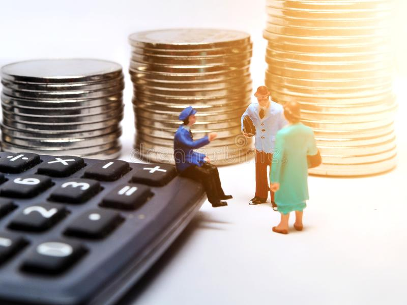 Miniature People walking on ruler with coin stacks. Concept of business people work calculated to success stock image