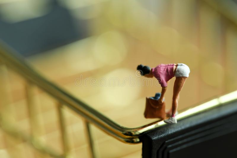 Miniature people : woman shopper with shopping cart,shopping con royalty free stock photo
